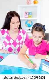 A mother helping her daughter with homework.