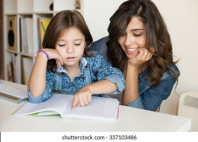 Mother helping her little child with homework