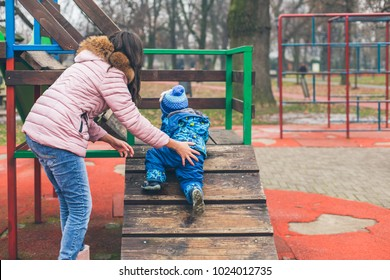 Mother helping her little son to climb  wooden stairs at playground