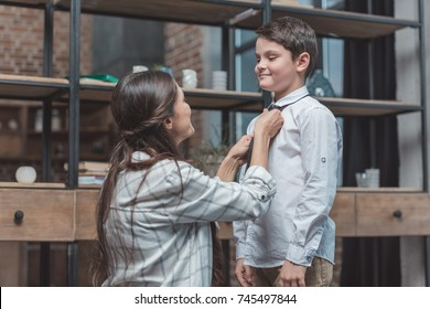 Mother helping her little son get dressed and tie a necktie