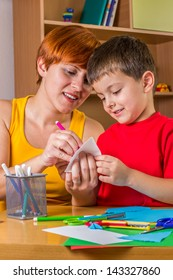 Mother helping her son to make paper craft