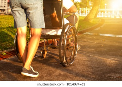 Mother helping her son on wheelchair up the ramp in the park with sunset in background, warm filter