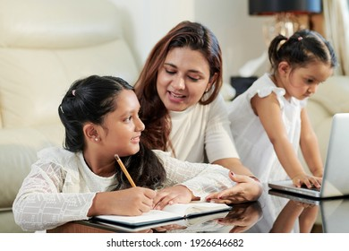 Mother helping her two daughters with doing homework for school when they are sitting at table in living room