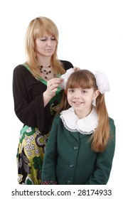 Mother is helping her's young daughter prepare to school. Woman is filleting ribbon on girl's hair.  Mom is brushing young schoolgirl's hair. Isolated on white in studio.