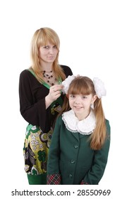 Mother is helping her's young daughter prepare to school. Woman is filleting ribbon on girl's hair.  Mom is brushing young schoolgirl's hair. Isolated on white in studio