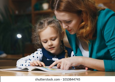 Mother helping kid after school. preschooler doing homework with help of tutor. home teaching concept.