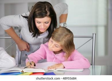 Mother helping little girl to do homework