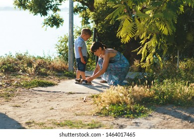mother helping son to clasp shoe in street