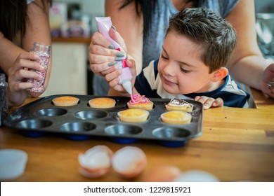 Mother helping son to put frosting onto cupcakes