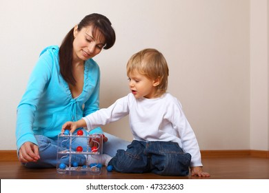 mother helping son put the toy
