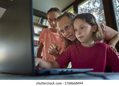 Mother helping for two girls infront of the laptop