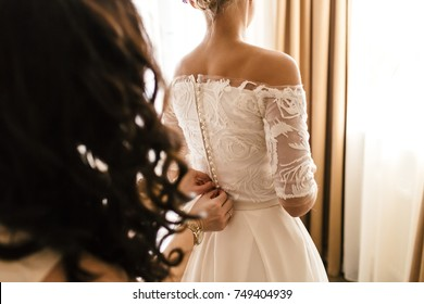 Mother helps fasten a wedding dress the bride before the ceremony. Wedding concept. Artwork