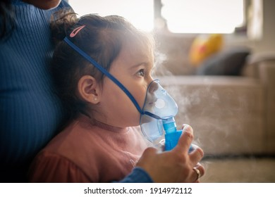 Mother helps her little girl to makes inhalation at home.During coronavirus COVID-19