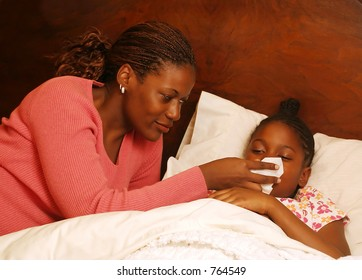 A mother helps her sick daughter blow her nose.