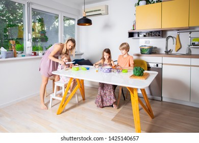 Mother helps hers tree children preparing food together in the kitchen.Happy and healthy family concept