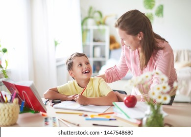 mother helps son to do lessons. home schooling, home lessons. the tutor is engaged with the child, teaches to write and count. out-of-school lessons with a teacher. happy baby in bright room with mom
