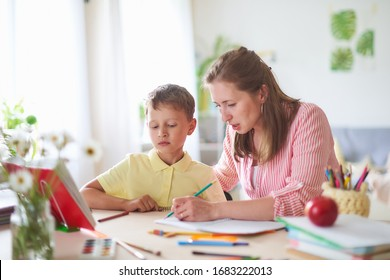 Mother helps son to do lessons. correct the error in home lessons. the tutor is engaged with child, teaches to write and count. out-of-school lessons with a teacher. happy baby in bright room with mom