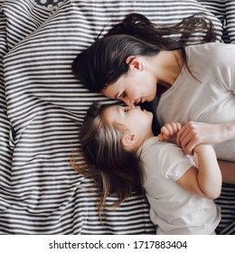 mother with her 3-year-old daughter lie face to face on the bed
