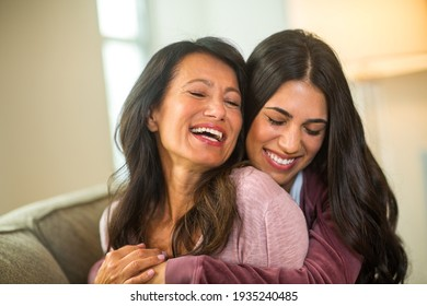 Mother and her adult daughter laughing at home