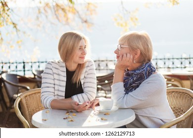 Mother and her adult daughter look at each other. Two beautiful women in cozy street cafe outside. Happy senior woman and young girl are smiling. Concept of kindness, family love, relationships