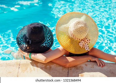 Mother and her adult daughter relaxing in hotel swimming pool. People enjoying summer vacation. Mother's day