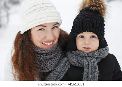 Mother and her baby boy having fun outdoors in winter.