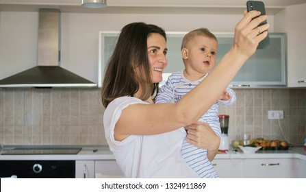 Mother and her baby boy take selfie on a smart phone  in the kitchen at home