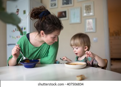 Mother with her baby eating soup in the bright kitchen at home,  real interior, Mom with dreadlocks, casual