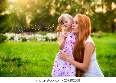 mother with her baby in the forest on the grass among the flowers together playing with dandelion and blowing it
