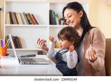 Mother and her baby girl listening to music on laptop.They sitting in living room.Natural light ambient.