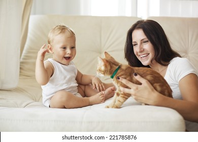 Mother with her baby playing with pet on a sofa at living room