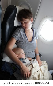 Mother with her baby are sleeping at airplane