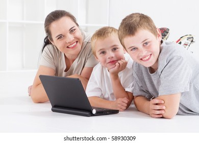 mother and her boys using laptop computer on floor