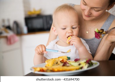 Mother with her child eating together and have a fun