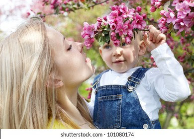Mother and her child enjoy the early spring between flowers.