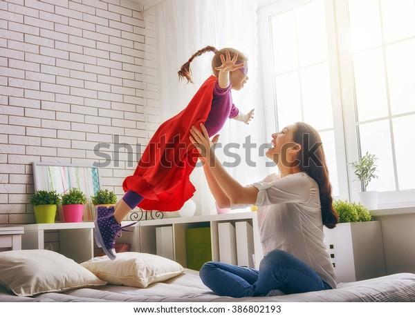 一緒に遊んでるお母さんと子ども。スーパーマンの衣装を着た女の子。子どもが楽しんでベッドで飛び上がった。