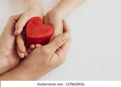 Mother and her child holding red heart in their hands on white background. Mother's Day background with copy space. International Hearth Day concept.