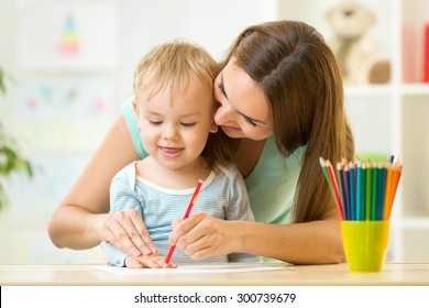 mother and her child pencil together at home