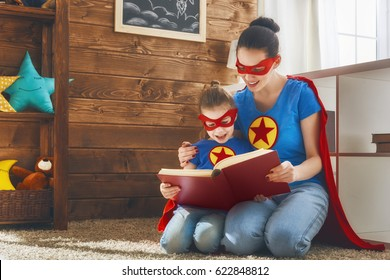 Mother and her child playing together. Girl and mom in Superhero costumes. Mum and kid having fun, smiling and reading a book. Family holiday and togetherness.