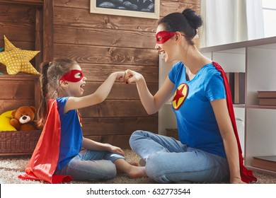 Mother and her child playing together. Girl and mom in Superhero costume. Mum and kid having fun, smiling. Family holiday and togetherness.