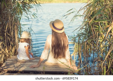Mother and her child playing together. Girl and mom wet feet in water. Mum and kid having fun. Family holiday and togetherness.Happy loving family.