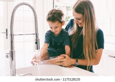 Mother with her child playing with water in kitchen sink at home. Happy lifestyle family moments.