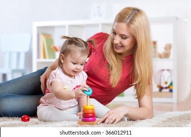 Mother with her child playing with wooden blocks at home