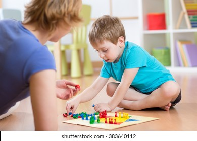 Mother and her child son playing in board game