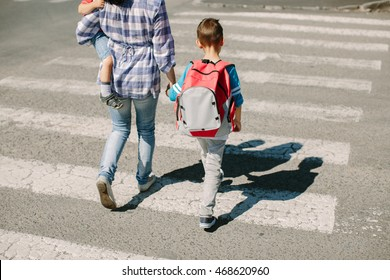 Mother and her children crossing road on way to school