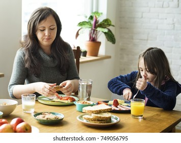 Mother with her children eating breakfast