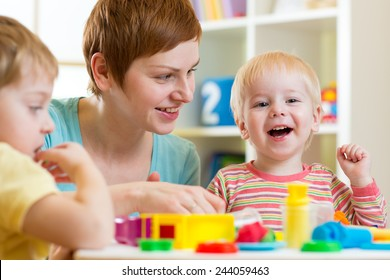 mother and her children have fun with colorful play clay toys