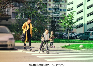 Mother and her children on zebra crossing. Woman guiding her son and daughter a cross the street.