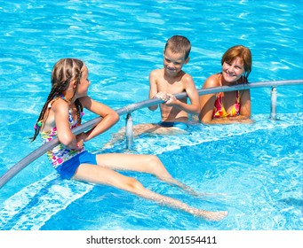 Mother with her children in the summer outdoor pool.