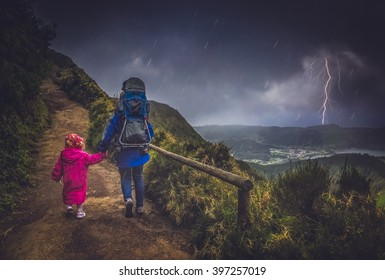 Mother and her children walking on a mountain trail in stormy and rainy weather, Sao Miguel, Azores, Portugal